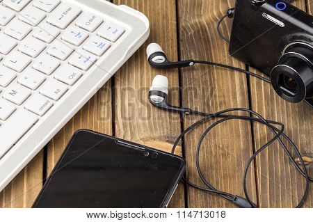 Laptop smart phone photo camera and headset on wooden background. poster