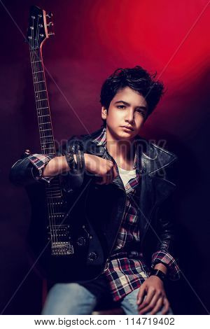 Portrait of handsome teen guitarist posing over dark red background, wearing trendy shirt and leather coat, cool teen's hobby