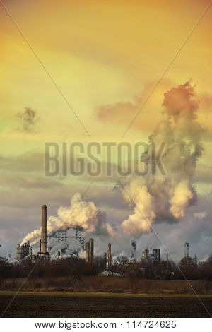 Oil refinery spewing gases from smoke stacks at sunset