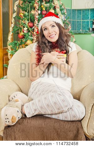 Smiling Woman Holding Gift Box Over Christmas Tree Decoration Background