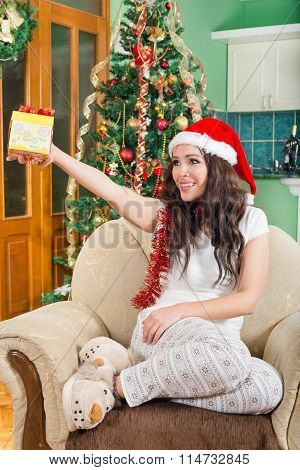 Young Woman In Santa Hat Proffers Gift Box With Ribbon