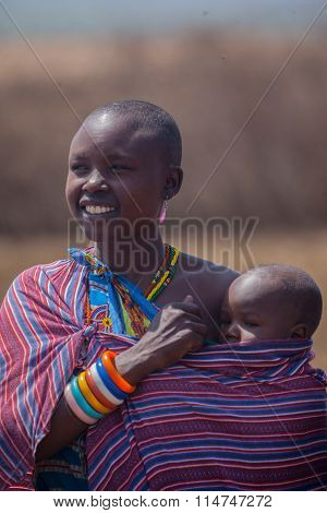 Smiling Masai mother holding her baby