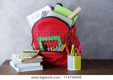 Backpack with school supplies on wooden table, on grey wall background