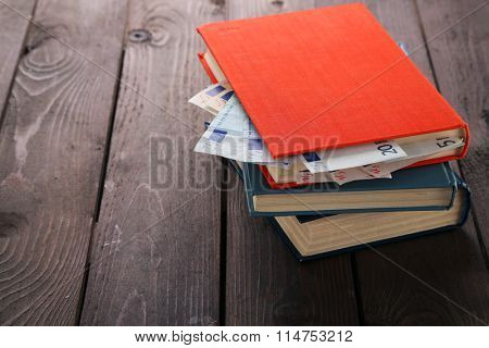 Books with nested euro banknotes on wooden table. Stash of money