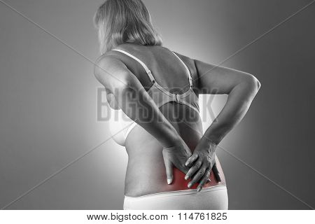 Woman With Backache. Pain In The Human Body On A Gray Background