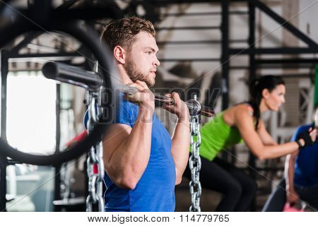 Man lifting dumbbell and chain in functional training gym session