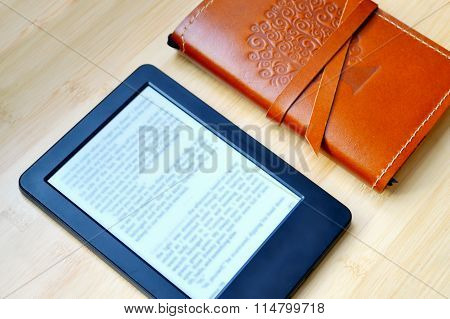 Black ereader with an old notebook in leather cover on wooden table