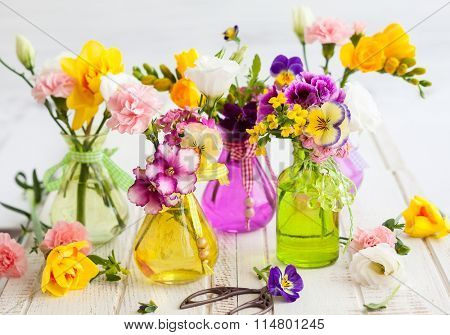 Beautiful fresh flowers in glass bottles on the wooden table