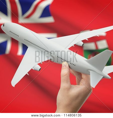 Airplane In Hand With Canadian Province Flag On Background - Manitoba