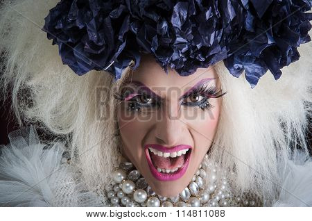 Closeup drag queen wearing spectacular makeup, glamorous trashy look, posing with open mouth for cam