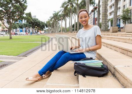 happy african college student with laptop sitting outdoors