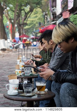 Asian people drinking coffee on the sidewalk