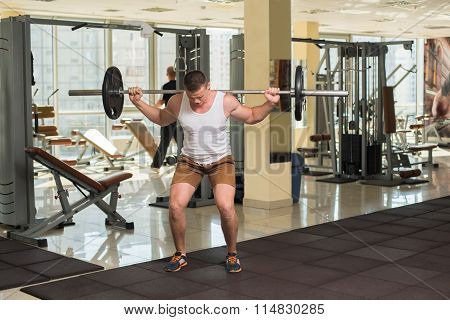 Bodybuilder with barbell in gym.