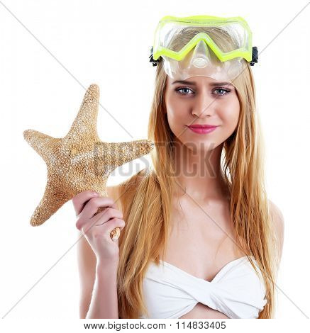 Young beautiful woman in swimsuit and diving mask holding starfish, isolated on white