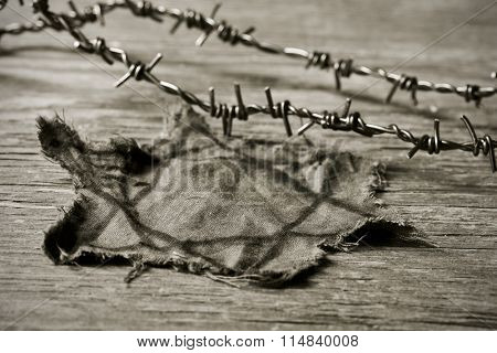 closeup of a Jewish badge and barbed wire on a rustic background, in sepia toning