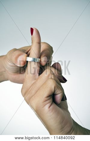 closeup of a man putting on or putting off a ring from the finger of a woman