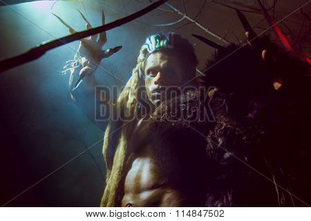 Werewolf With Long Nails And Crooked Teeth Among The Branches Of The Tree And Smoke