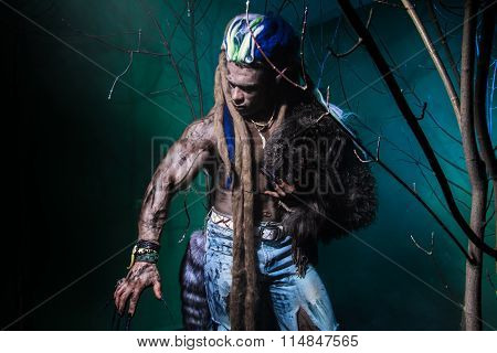 Muscular Werewolf With Dreadlocks With Long Nails Among The Branches Of The Tree.