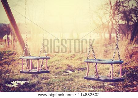 Vintage Stylized Two Neglected Empty Swings.
