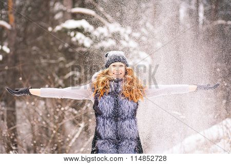 Girl In Winter Clothes Throwing Snow Up In Air