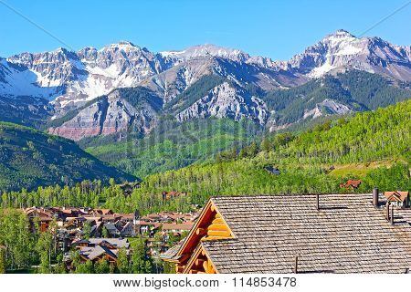 Telluride city panorama with snow mountain peaks and forestry hillsides.