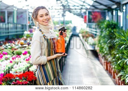 Beautiful happy young woman gardener in striped apron holding water sprayer in greenhouse