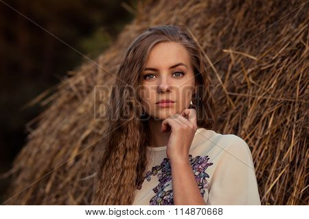 Lovely, beautiful, nice, cute, pretty, sexy, serious girl near the hay, with long, light, magnificent hair, brown hay, field of hay, drain hay lean on chin, has jacket with patterns, slender, graceful fingers, fresh