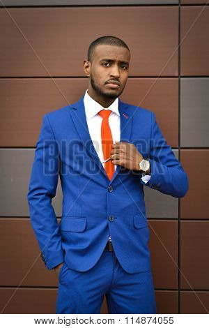 African, young, successful, cheerful, sincere smile, satisfied businessman corrects tie, corporate, leader, office, work, executive, style, businessman, smart, wise, clever, contemporary, handsome, foreigner, Uzbek, male
