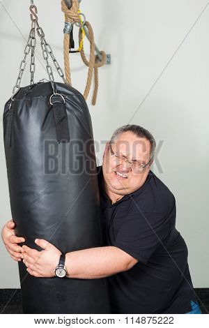 Fat Man Struggling With A Punching Bag In The Gym