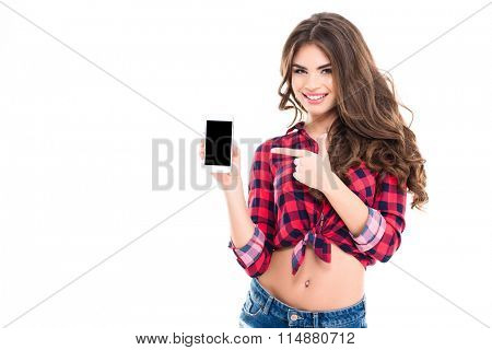 Happy beautiful young woman with long curly hair holding blank screen mobile phone and pointing on it over white background