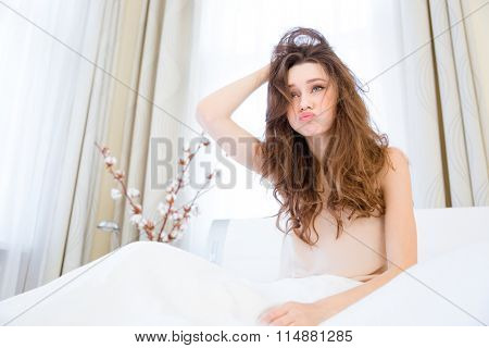 Funny pretty sleepy young woman with tousled hair sitting on bed at home