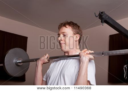 Young skinny man front loads barbell