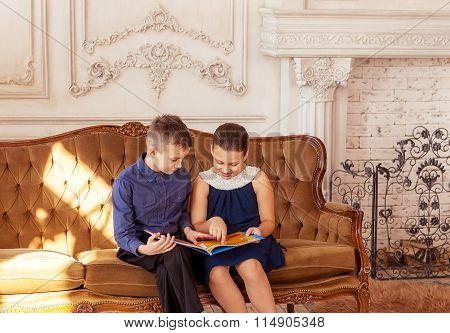 Beautuful children sit on sofa and read