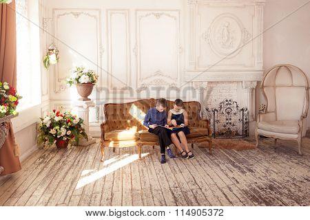 Children reading book in living room