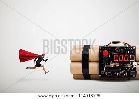 superwoman in red cloak and mask ready to defusing big bomb with timer over light grey background