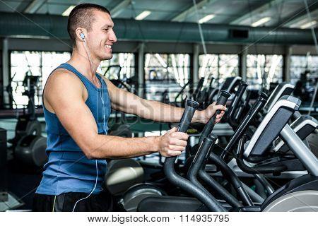 Smiling muscular man using elliptical machine at gym