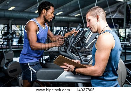 Muscular man using elliptical machine with trainer at gym