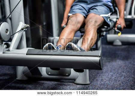 Cropped image of man using exercise machine at gym