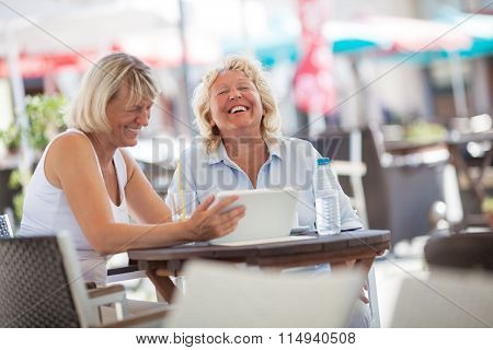Senior women laughing while using tablet PC in cafe
