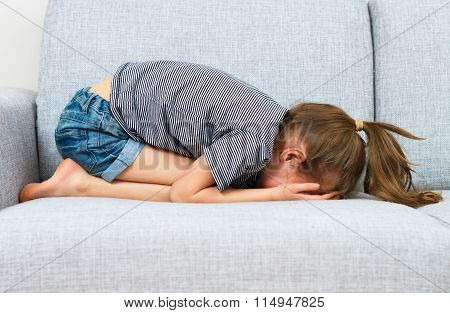 Sad Little Girl Crying On The Sofa.