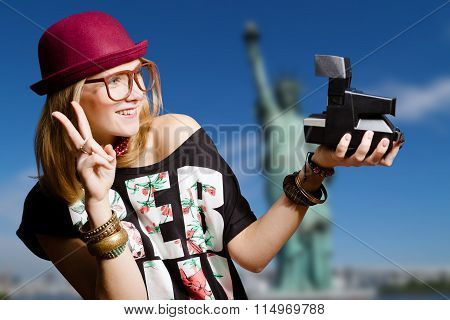 Beautiful young woman making selfie by polaroid in New York