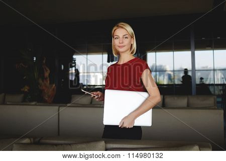 Female entrepreneur posing with cellphone and laptop after successful meeting