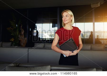 Woman in good mood looking away while standing with digital tablet in modern interior
