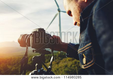 Young man photographing beautiful calm wild nature with camera of while standing against wind turbin