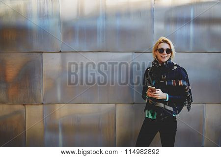 Cheerful young woman holding cell telephone and smile to the camera