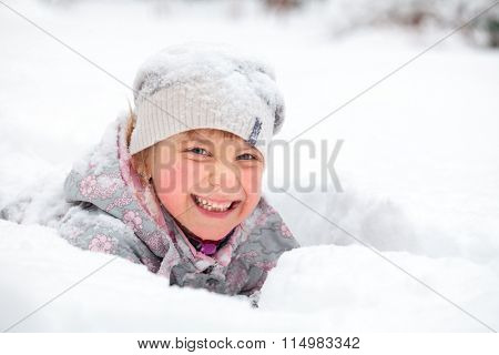 Little girl wearing winter clothing having fun laying in a fresh snow