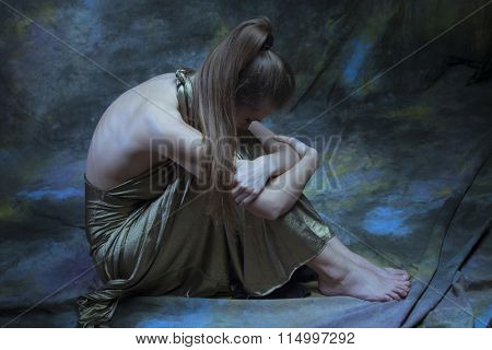depressed barefoot woman in long elegant golden dress  sit on  floor,  full body shot, above