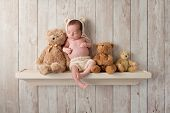 Three week old newborn baby boy wearing a cream colored crocheted bear bonnet. He is sleeping on a shelf next to three Teddy Bears. Shot in the studio on a dark wood background. poster