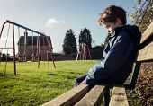 Upset problem child sitting on play park playground bench concept for bullying, depression, child protection or loneliness poster