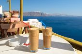 Ice coffee frape at balcony view on caldera of Santorini island, Greece poster
